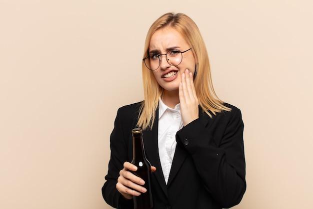 Junge blonde frau, die wange hält und schmerzhafte zahnschmerzen leidet, sich krank, elend und unglücklich fühlt und einen zahnarzt sucht