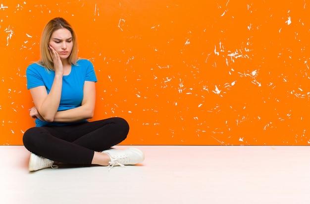 Junge blonde frau, die wange hält und schmerzhafte zahnschmerzen leidet, sich krank, elend und unglücklich fühlt und nach einem zahnarzt sucht, der auf dem boden sitzt