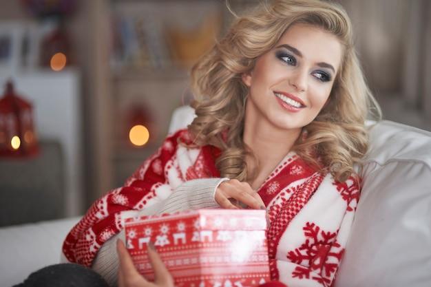 Junge blonde frau, die weihnachtsgeschenk hält