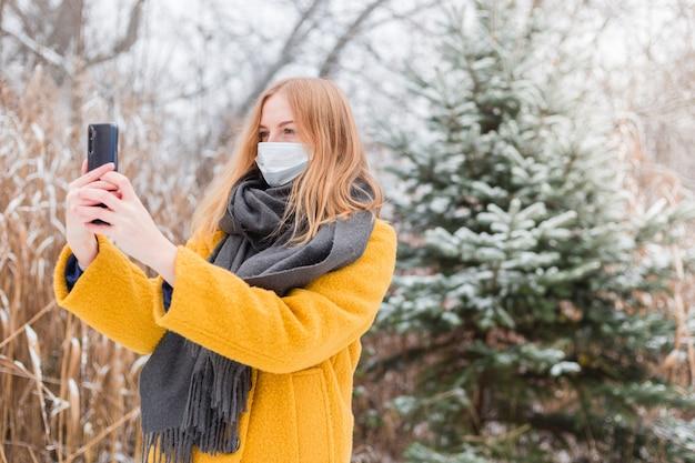 Junge blonde frau, die weiße medizinische gesichtsmaske mit smartphone-app über naturhintergrund, trendige farben des jahres 2021 trägt - leuchtendes gelb und ultimatives grau. covid-19