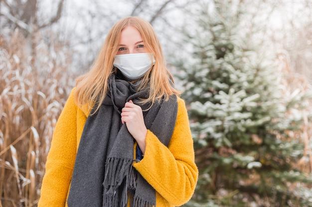 Junge blonde frau, die weiße medizinische gesichtsmaske über naturhintergrund, trendige farben des jahres 2021 trägt - leuchtendes gelb und ultimatives grau. covid-19 pandemisches coronavirus