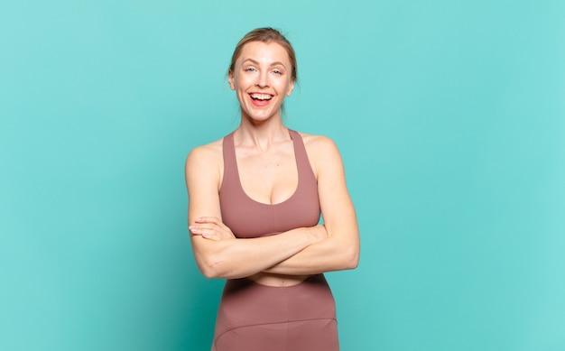 Junge blonde frau, die wie ein glücklicher, stolzer und zufriedener leistungsträger aussieht, der mit verschränkten armen lächelt. sportkonzept