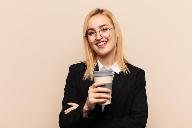 Junge blonde frau, die wie ein glücklicher, stolzer und zufriedener leistungsträger aussieht, der mit verschränkten armen lächelt