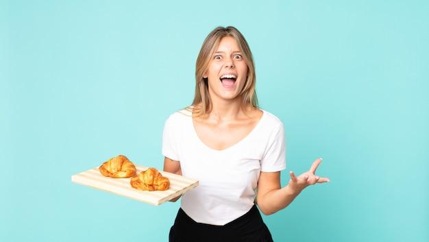 Junge blonde frau, die wütend, verärgert und frustriert aussieht und ein croissant-tablett hält