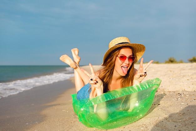 Junge blonde frau entspannen und genießen sie ihre sommerferien, legen sie sich auf luftmatratze und nehmen sie ein sonnenbad, helle stilvolle strandkleidung hut und sonnenbrille