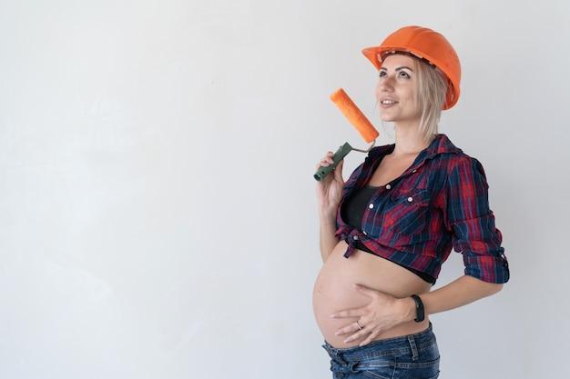 Junge blonde frau, gekleidet in einem karierten hemd und einem orangefarbenen bauhelm auf weißem hintergrund. schwangeres mädchen. halten sie den farbroller fest. platz kopieren.