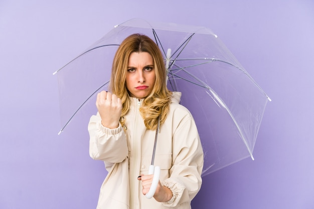 Junge blonde frau hält einen regenschirm isoliert junge blonde frau hält einen regenschirm isoliert zeigt faust zur kamera, aggressiver gesichtsausdruck.