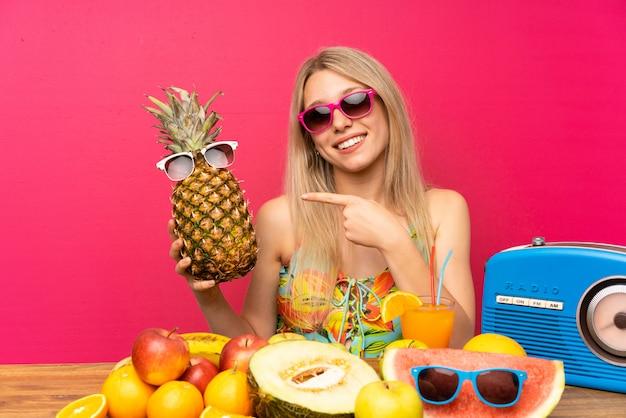 Junge blonde frau im badeanzug, der eine ananas mit sonnenbrillen anhält