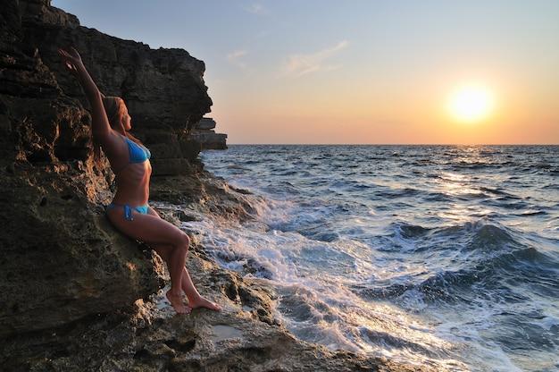 Junge blonde frau im bikini, der auf felsen steht und tropfen der wellen und des sonnenuntergangs am sommertag genießt. konzept für glück, urlaub und freiheit