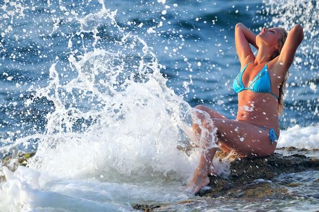 Junge blonde frau im blauen bikini, der auf felsen sitzt und tropfen der wellen am klaren sonnigen sommertag genießt. konzept für glück, urlaub und freiheit