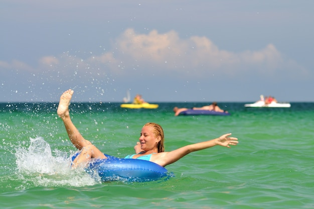 Junge blonde frau im blauen bikini, der auf schwimmkreis im meer reitet und am sonnigen sommertag lächelt. konzept für glück, urlaub und freiheit
