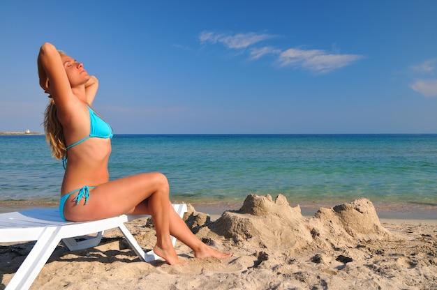 Junge blonde frau im blauen bikini, der auf sonnenliege nahe stillem meerwasserrand liegt und sonnenschein am sonnigen sommertag genießt. konzept für glück, urlaub und freiheit