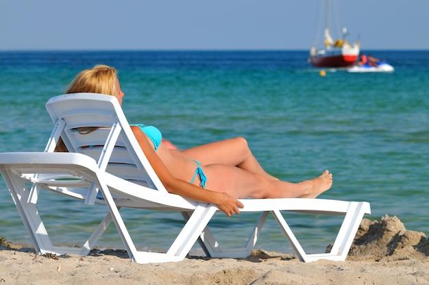 Junge blonde frau im blauen bikini, der auf sonnenliege nahe stillem meerwasserrand liegt