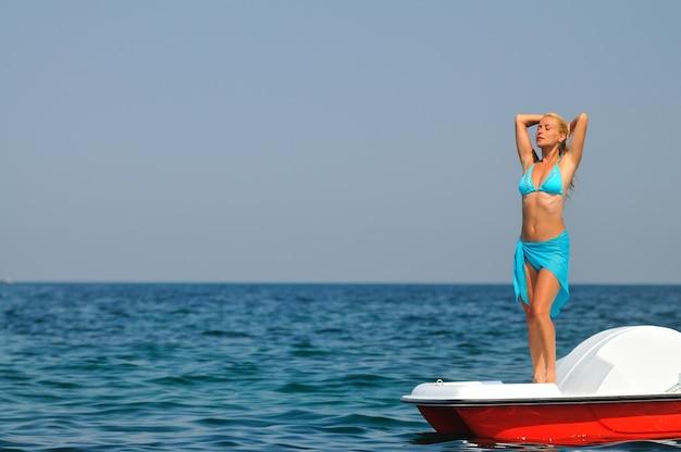 Junge blonde frau im blauen bikini, der auf weißem katamaran steht
