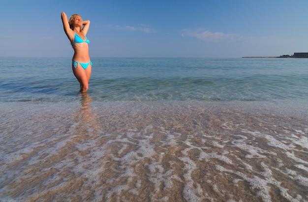 Junge blonde frau im blauen bikini, der im stillen meerwasser steht und sonnenschein am sonnigen sommertag genießt. konzept für glück, urlaub und freiheit