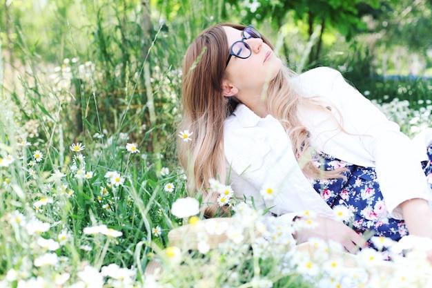 Junge blonde frau im park liegt in kamille