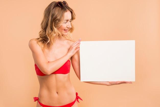 Junge blonde frau im roten bikini, der leeres brett hält