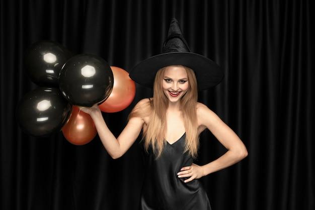 Junge blonde frau im schwarzen hut und im kostüm auf schwarz