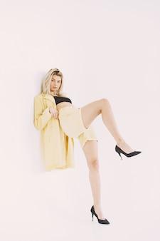 Junge blonde frau im stilvollen gelben anzug. kamera auf weiß betrachten.