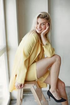 Junge blonde frau im stilvollen gelben anzug. kamera auf weiß betrachten. Kostenlose Fotos