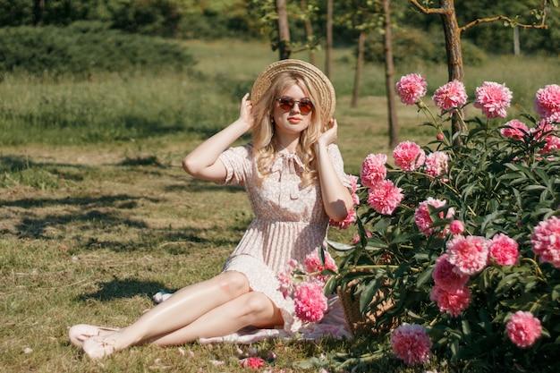 Junge blonde frau im strohhut nahe blumenbeet mit pfingstrosen, sommerfoto