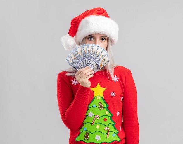 Junge blonde frau im weihnachtspullover und in der weihnachtsmannmütze, die bargeld hält, das mit ernstem gesicht schaut