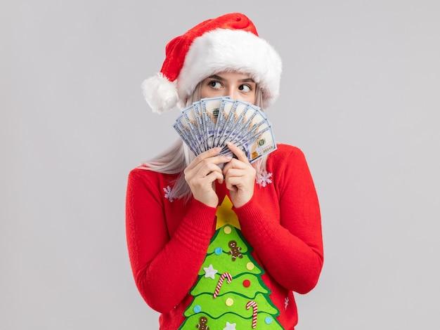 Junge blonde frau im weihnachtspullover und in der weihnachtsmannmütze, die bargeld halten, das mit ernstem gesicht beiseite schaut
