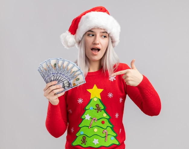 Junge blonde frau im weihnachtspullover und in der weihnachtsmannmütze, die bargeld zeigt mit zeigefinger auf geld glücklich und überrascht