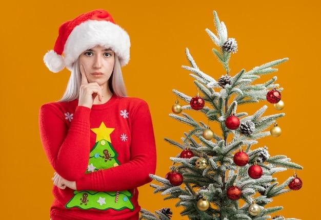 Junge blonde frau im weihnachtspullover und in der weihnachtsmannmütze, die kamera mit der hand auf kinn denkend mit ernstem gesicht betrachten, das nahe an einem weihnachtsbaum über orange hintergrund steht