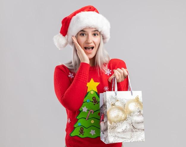 Junge blonde frau im weihnachtspullover und in der weihnachtsmannmütze, die papiertüten mit weihnachtsgeschenken hält, die erstaunt und überrascht schauen
