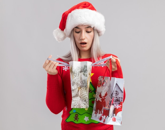 Junge blonde frau im weihnachtspullover und in der weihnachtsmannmütze, die papiertüten mit weihnachtsgeschenken halten, die taschen suchen, die fasziniert schauen