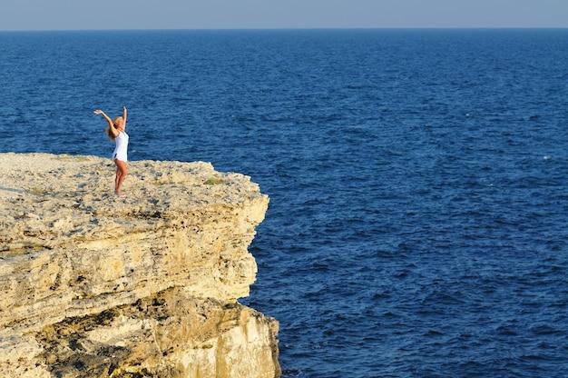 Junge blonde frau im weißen minikleid, das auf felsen über meerwasser steht und horizont am klaren sonnigen sommertag betrachtet. konzept für glück, urlaub und freiheit