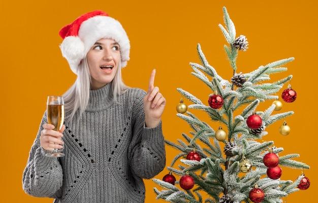 Junge blonde frau im wintergrauen pullover und in der weihnachtsmannmütze, die glas champagner hält, der mit zeigefinger oben glücklich und fröhlich steht, steht neben einem weihnachtsbaum über orange hintergrund