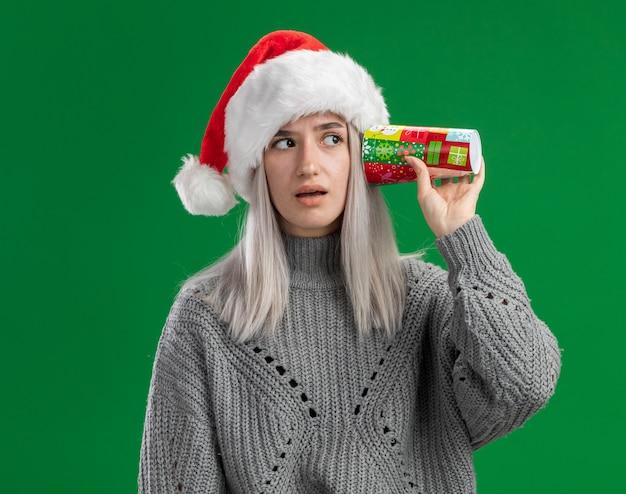Junge blonde frau im winterpullover und in der weihnachtsmannmütze, die bunte pappbecher über ihrem ohr hält, das fasziniert steht, über grünem hintergrund stehend