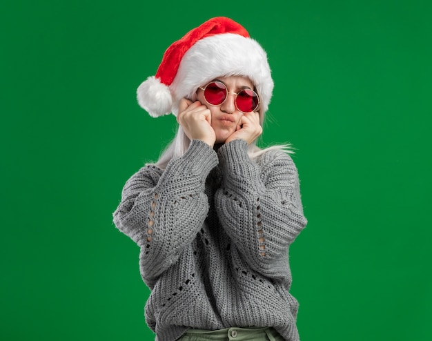 Junge blonde frau im winterpullover und in der weihnachtsmannmütze, die die rote brille tragen, die kamera betrachtet, die grimasse macht, die spaß hat, über grünem hintergrund zu stehen