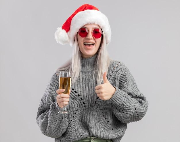 Junge blonde frau im winterpullover und in der weihnachtsmannmütze, die glas champagner hält, zeigt daumen hoch glücklich und positiv