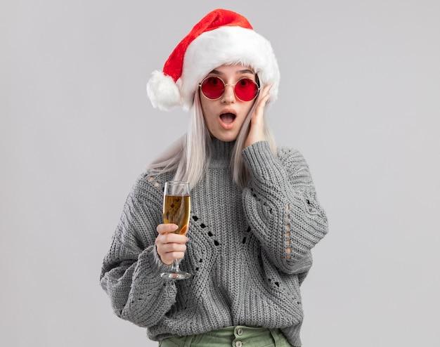 Junge blonde frau im winterpullover und in der weihnachtsmannmütze, die glas champagner halten, der erstaunt schaut