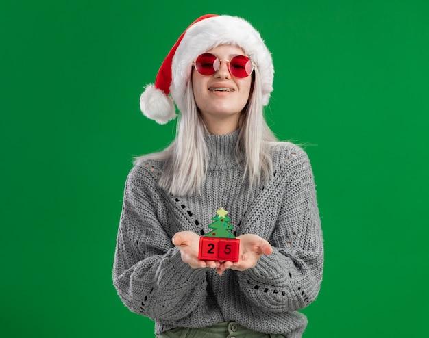 Junge blonde frau im winterpullover und in der weihnachtsmannmütze, die rote brille hält, die spielzeugwürfel mit weihnachtsdatum glücklich und positiv betrachtet, die kamera lächelnd steht über grünem hintergrund