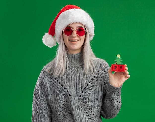 Junge blonde frau im winterpullover und in der weihnachtsmannmütze, die rote brille hält, die spielzeugwürfel mit weihnachtsdatum hält, das kamera glücklich und positiv lächelnd steht über grünem hintergrund