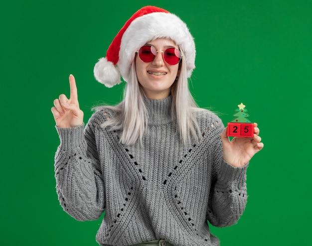 Junge blonde frau im winterpullover und in der weihnachtsmannmütze, die rote brille hält, die spielzeugwürfel mit weihnachtsdatum hält, das kamera glücklich und positiv zeigt zeigefinger steht über grünem hintergrund