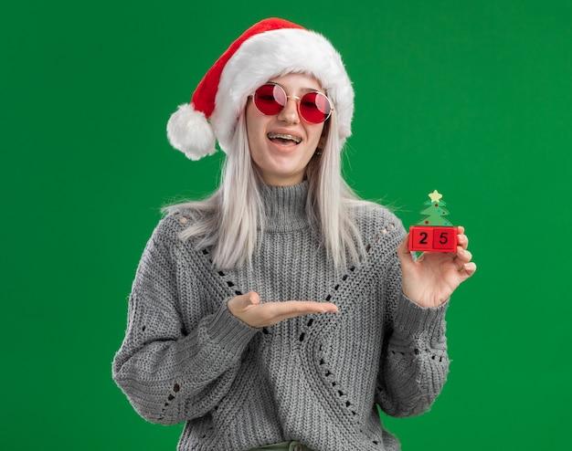 Junge blonde frau im winterpullover und in der weihnachtsmannmütze, die rote brille hält, die spielzeugwürfel mit weihnachtsdatum hält, das mit arm glücklich und positiv steht über grünem hintergrund