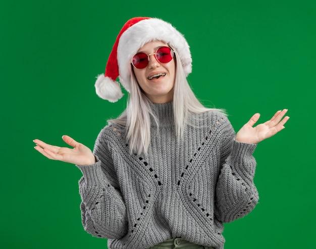 Junge blonde frau im winterpullover und in der weihnachtsmannmütze, die rote gläser tragen, die kamera glücklich und positiv lächelnd fröhlich stehen über grünem hintergrund betrachten