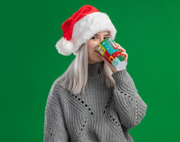 Junge blonde frau im winterpullover und in der weihnachtsmannmütze, die vom bunten pappbecher glücklich und positiv stehen über grünem hintergrund trinken