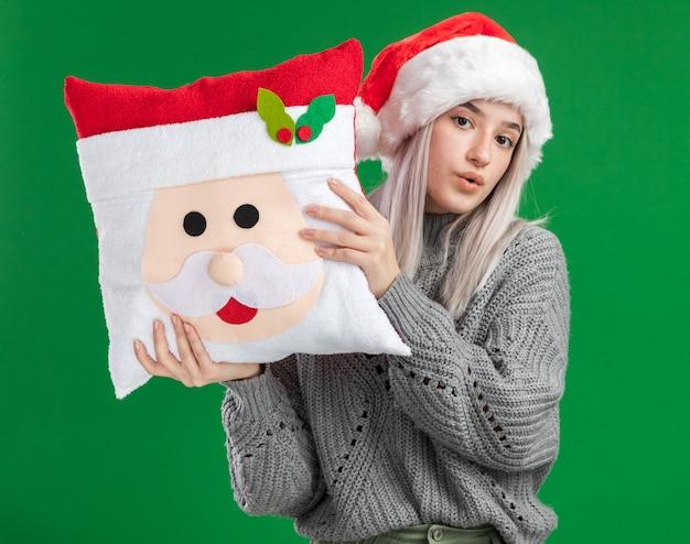 Junge blonde frau im winterpullover und in der weihnachtsmannmütze, die weihnachtskissen betrachten kamera mit dem sicheren ausdruck stehen über grünem hintergrund