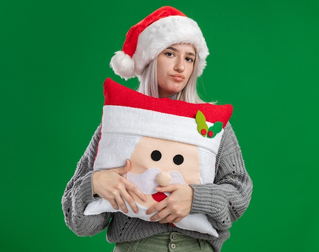Junge blonde frau im winterpullover und in der weihnachtsmannmütze, die weihnachtskissen halten, das kamera mit stirnrunzelndem gesicht betrachtet, das über grünem hintergrund nicht steht