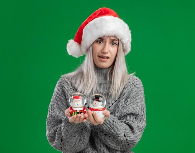 Junge blonde frau im winterpullover und in der weihnachtsmannmütze, die weihnachtsspielzeug-schneekugeln betrachten, die die kamera verwirrt betrachten, die über grünem hintergrund steht