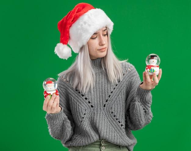 Junge blonde frau im winterpullover und in der weihnachtsmannmütze, die weihnachtsspielzeug-schneekugeln halten, die verwirrt versuchen, wahl zu treffen, die über grünem hintergrund steht