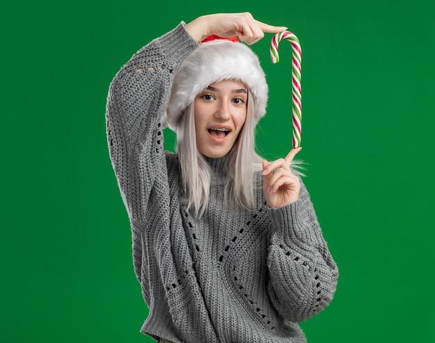 Junge blonde frau im winterpullover und in der weihnachtsmannmütze, die zuckerstange glücklich und fröhlich betrachten kamera betrachten, die über grünem hintergrund steht