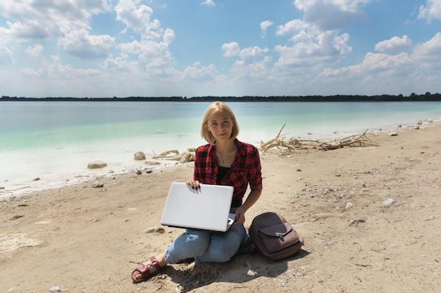 Junge blonde frau in den jeans und im hemd arbeitet an einem computer beim sein auf der natur.