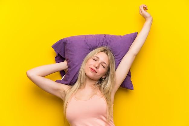 Junge blonde frau in den pyjamas gähnend